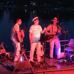 Zu sehen sind die drei Band Mitglieder von Southern Cross auf einer Floßbühne
